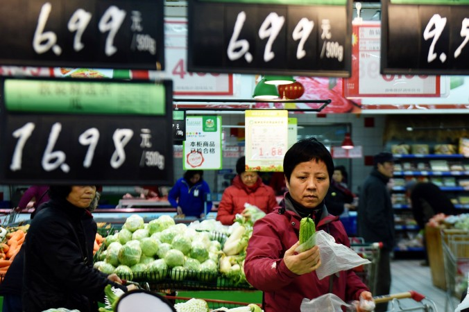 Покупатели выбирают овощи в супермаркете в Ханчжоу, провинция Чжэцзян, 10 марта 2016 г. Фото: STR/AFP/Getty Images