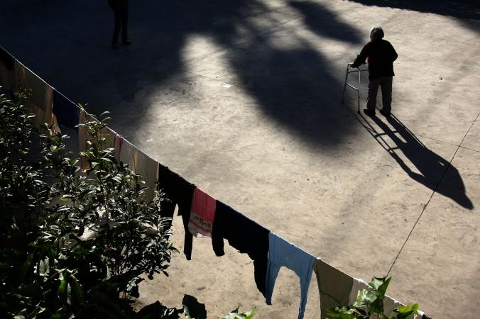 Старик ходит по двору в доме престарелых в Куньмине, провинция Юннань, Китай, 12 декабря 2007 г. Две трети обитателей этого дома престарых страдают от старческого слабоумия. Население Китая стремительно стареет. В настоящее время в стране свыше 140 миллионов пожилых людей. В ближайшее 50 лет их число увеличится на 3,2%. Фото: China Photos/Getty Images