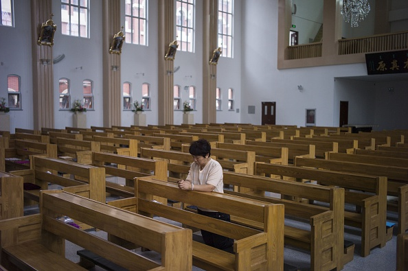 Женщина молится в католической церкви в Тяньцзине 7 июня 2015 года. Многие церкви в китайской провинции Чжэцзян превращены в культурные центры. Фото: Fred Dufour/AFP/Getty Images