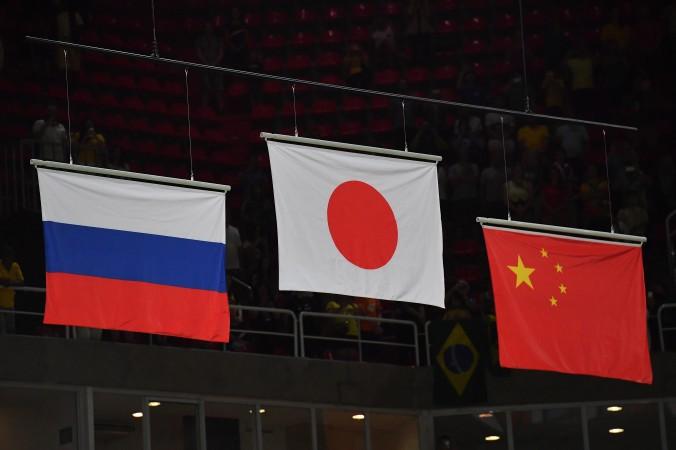Слева направо: российский, японский и китайский флаги на олимпийской арене, 8 августа 2016 года. Фото: Бен Stansall/AFP/GettyImages