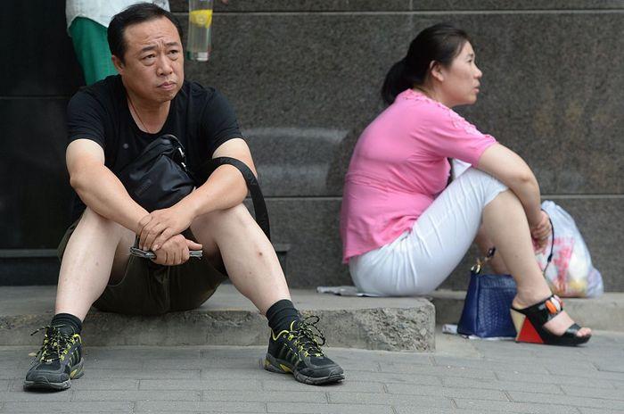 Родители в ожидании своих детей, сдающих вступительные экзамены в колледж в Пекине. Фото: STR / AFP / Getty Images