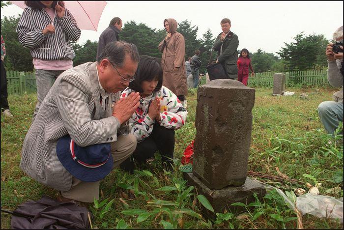 Японская семья посетила могилу своих родственников на острове Кунашире (Южные Курилы). Фото: JUNJI KUROKAWA/AFP/Getty Images