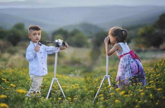 Дети фотографируются в поле с ромашками