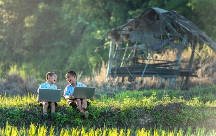 два мальчика сидят на траве с ноутбуками и смеются