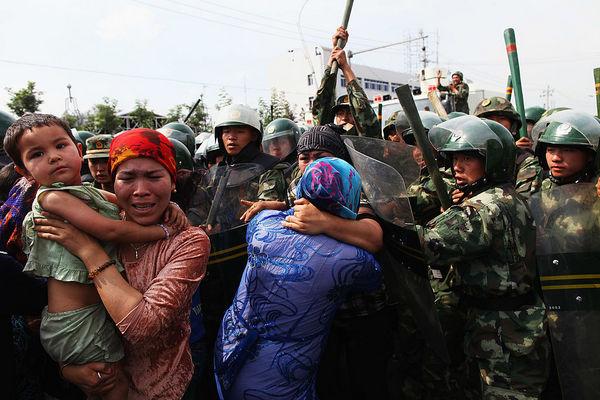 Китайские полицейские толкают протестующих уйгурских женщин в Урумчи, столице Синьцзяна