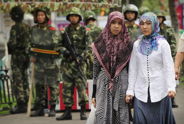 Две уйгурские женщины проходят мимо китайских военизированных полицейских в уйгурском районе города Урумчи, Синьцзян.
