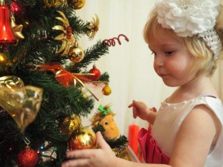 Новый год без пожара. Девочка рядом с украшенной ёлкой
