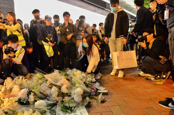 Люди приносят цветы в память о о протестующем Марко Люне