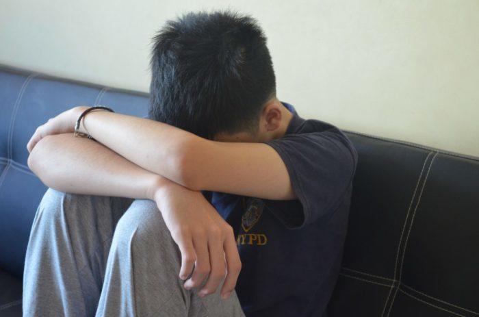 мальчик-подросток сидит на диване, опустив голову