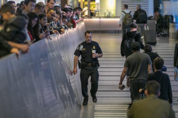 вирусная пневмония в Китае. Офицер аэропорта в Калифорнии проходит мимо пассажиров, прибывающих из Уханя