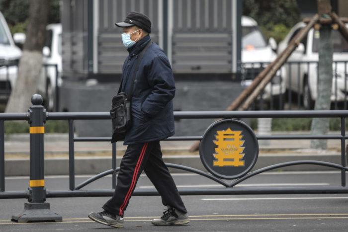 Вирусная пневмония в Китае. Пожилой мужчина в маске проходит мимо закрытого оптового рынка морепродуктов Хуанань в Ухане