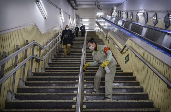 Уханьский коронавирус. Работница дезинфицирует перила в вечерний час пик в Пекине