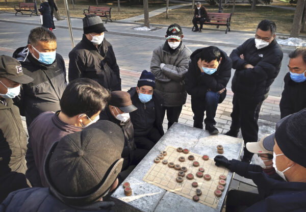 коронавирус COVID-19,Мужчины в масках играют в маджонг в парке Пекина, Китай