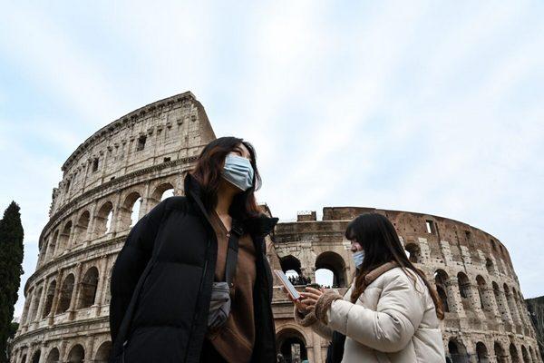Туристы в защитных масках у Колизея в центре Рима, Италия