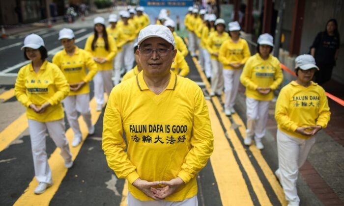 Сторонники духовной практики Фалуньгун принимают участие в марше в Гонконге 27 апреля 2019г.