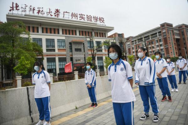 Учащиеся средней школы города Гуанчжоу, Китай, выстраиваются в очередь на тестирование COVID-19