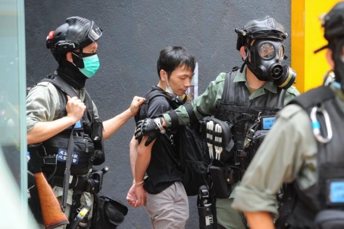 Протестующий, одетый в чёрное, был закован полицией в наручники на Хеннесси-Роуд в Козуэй-Бэй, Гонконг, 24 мая 2020 года.