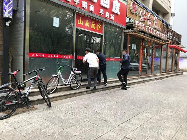 Три человека заглядывают внутрь закрытого ресторана