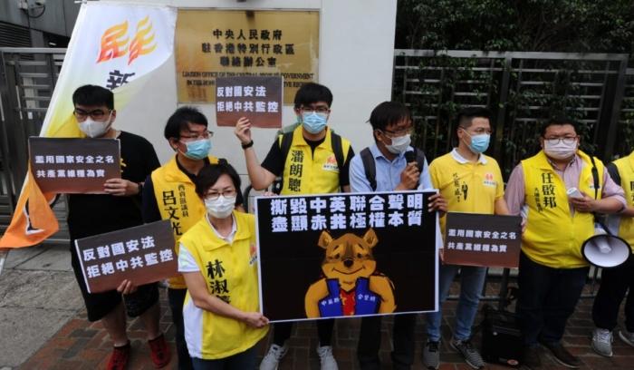 Члены продемократической партии «Нео-демократы» проводят акцию протеста у здания Гонконгского отделения связи в Гонконге 24 мая 2020 года