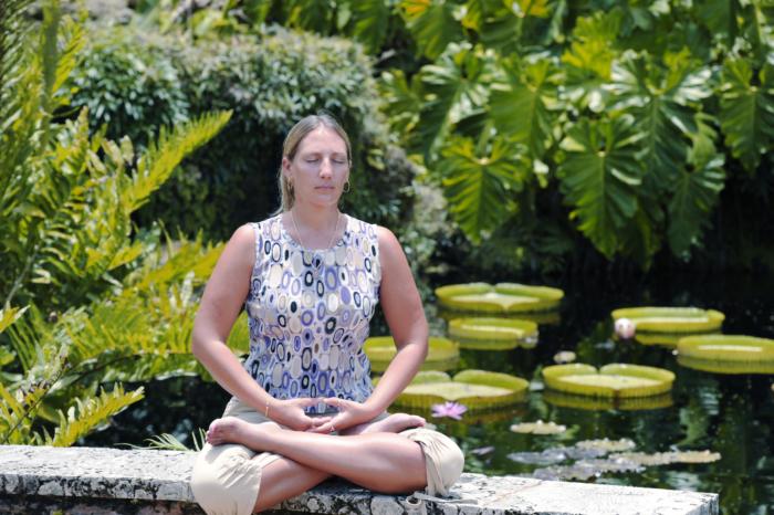 женщина медитирует возле пруда с лотосами