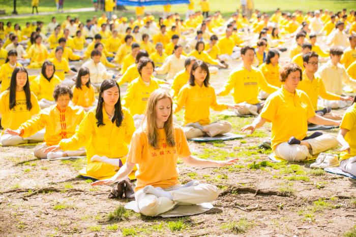 практикующие Фалуньгун в жёлтых одеждах медитируют