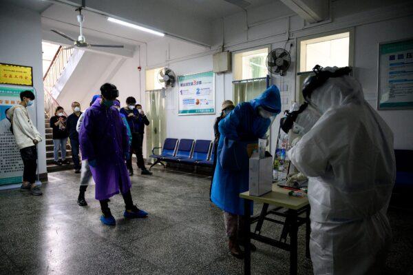 Люди ждут тестирования на COVID-19 в больнице № 8 города в Ухане