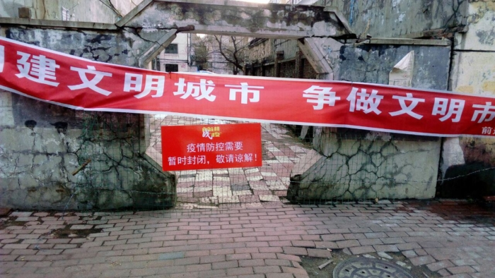 Некоторые жилые комплексы в районе Цяньцзинь снова закрыты, на двери висит большой горизонтальный баннер и предупреждающая табличка