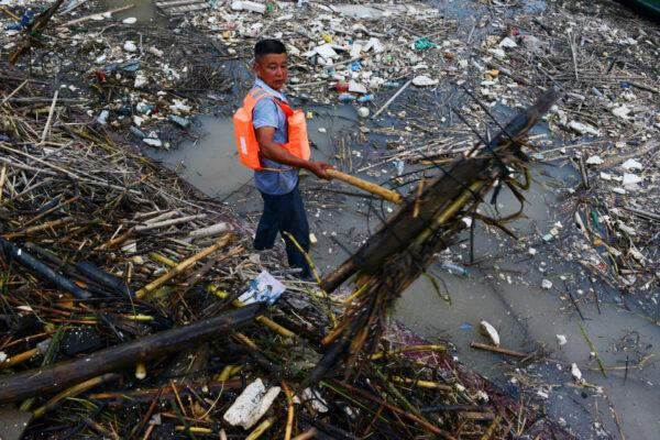 Рабочий собирает мусор в районе водохранилища «Три ущелья»