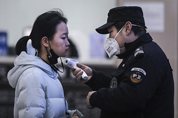 Сотрудники службы безопасности проверяют температуру пассажиров в Ухане