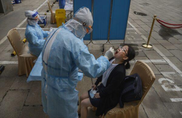 Китайский медработник проводит тест на нуклеиновую кислоту у журналиста, освещающего Всекитайское собрания народных представителей в Пекине 28 мая 2020г.