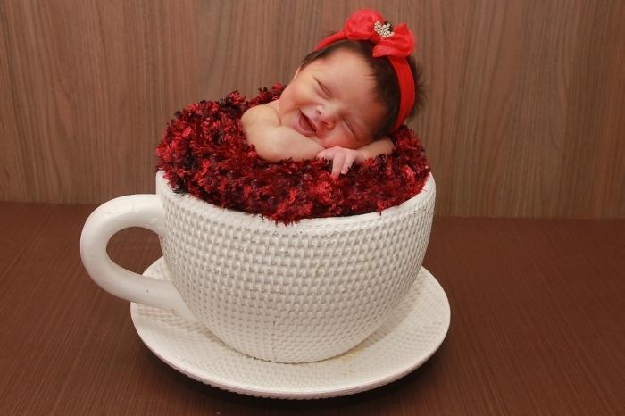 Новорождённая девочка улыбается во сне.