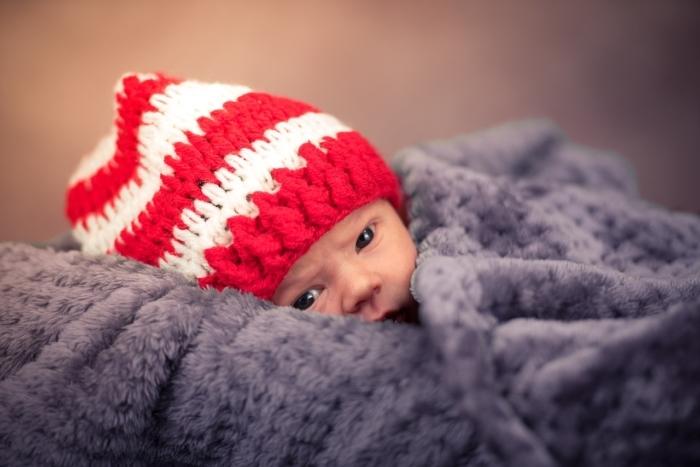 Новорождённый в шапке и под одеялом.