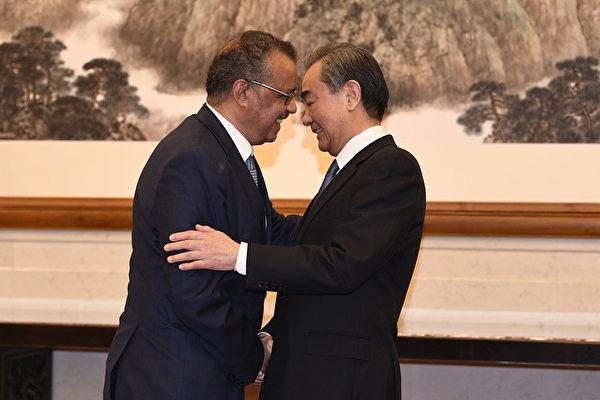 Тедрос Аданом Гебреисус, Генеральный директор ВОЗ, пожимает руку министру иностранных дел КНР Ван И.