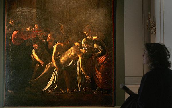 Женщина смотрит на картину Караваджо «Воскрешение Лазаря»