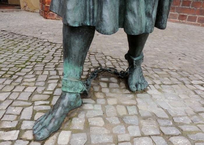 Статуя человека с кандалами на ногах