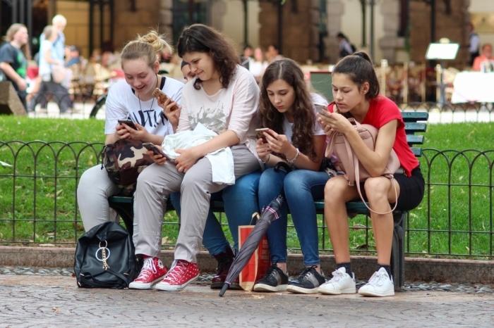 Группа девочек-подростков смотрят в телефоны