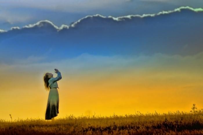 женщина молитвенно сложила руки и смотрит в небо