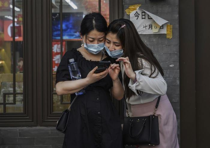 Жительницы Пекина смотрят в мобильный телефон