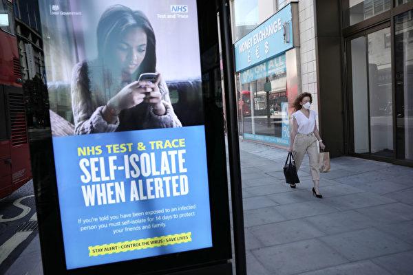 Женщина проходит мимо рекламы NHS Test and Trace на Оксфорд-стрит