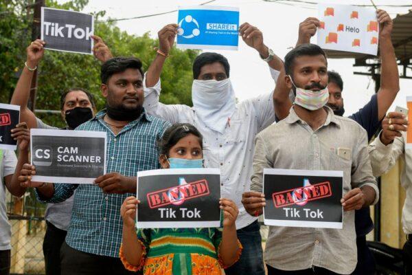 Члены городской молодёжной организации держат плакаты с логотипами китайских приложений в Хайдарабаде