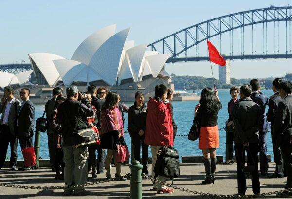 Группа азиатских туристов фотографируется перед Сиднейским оперным театром и мостом Харбор-Бридж