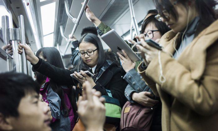 Пассажиры смотрят фильмы на мобильных телефонах и планшетах в китайском метро