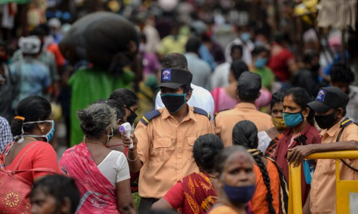 Сотрудник службы безопасности проверяет температуру женщины в Индии