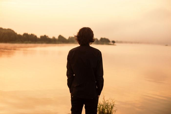 парень смотрит озеро