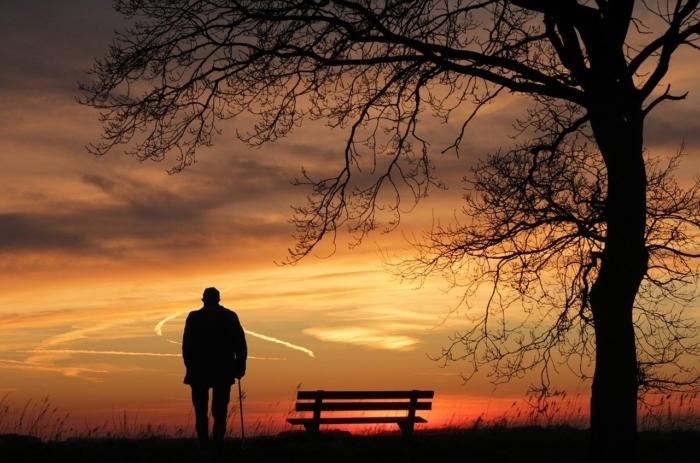 Пожилой человек смотрит на закат