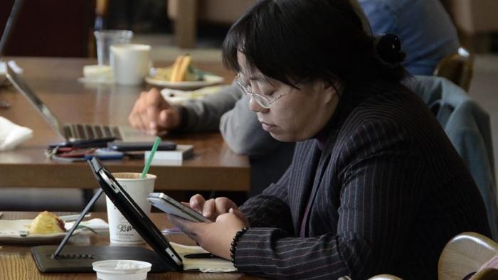 Посетители кафе выходят в интернет со смартфонов и ноутбуков в Пекине