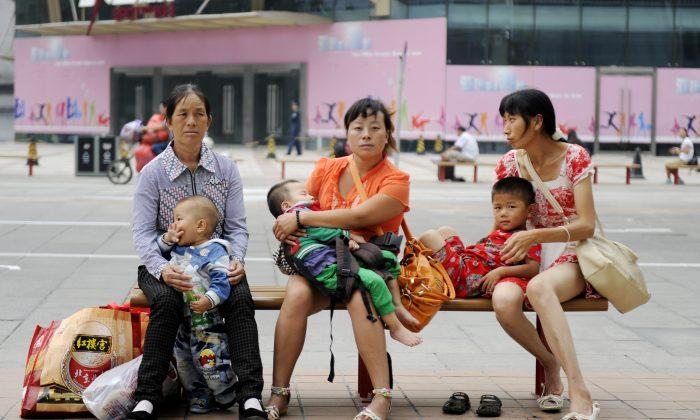 Женщины с детьми сидят на уличной скамейке в Пекине