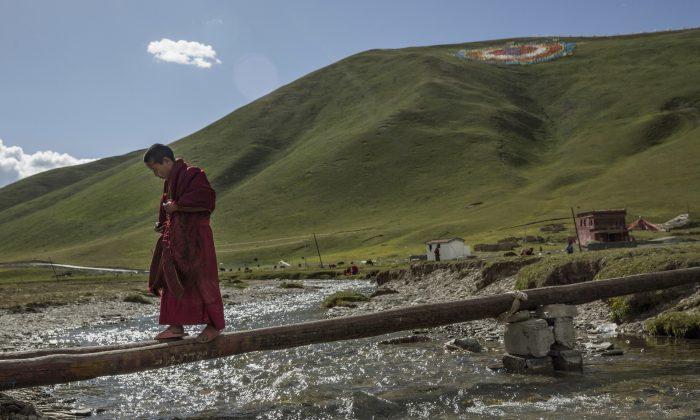 Молодой тибетский буддийский монах переходит ручей рядом с правительственной общиной переселенцев для бывших кочевников на Тибетском плато