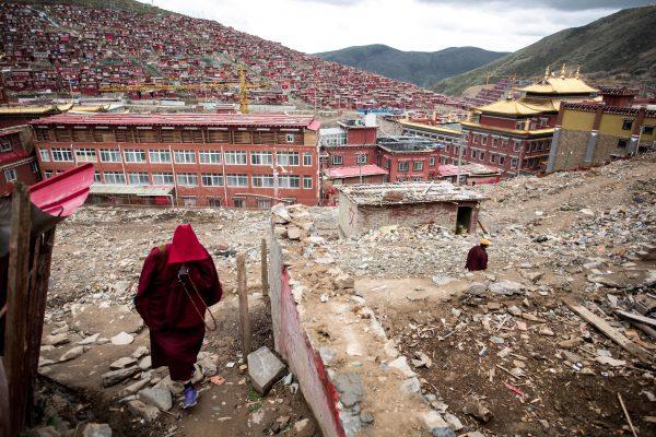 Монахиня гуляет среди обломков разрушенных домов в главнейшем учебном заведении тибетского буддизма, монастыре Ларунг Гар в Китае
