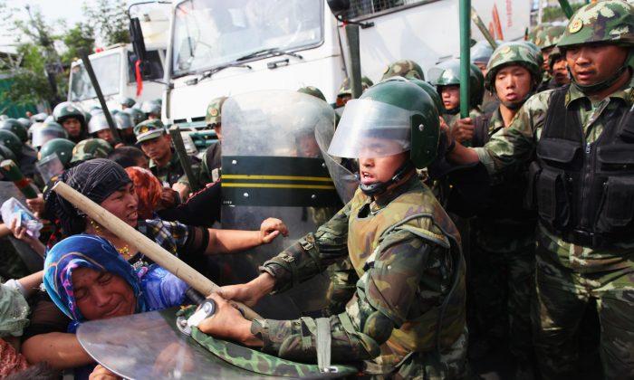 Китайские полицейские разгоняют уйгурских женщин на улице города Урумчи, Синьцзян, Китай, 7 июля 2009 года